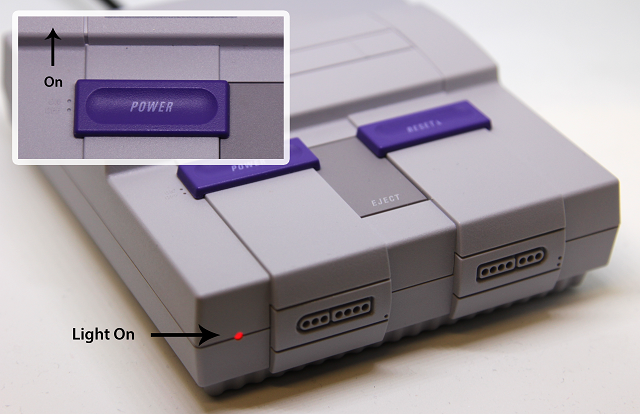 Photo of the SNES Classic Edition showing the power switch in the on position, and the power LED lit in a red color.