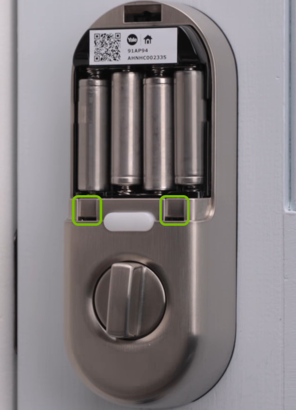 Holes holding the battery cover tabs annotated on door lock.