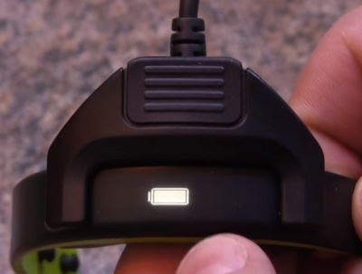 Garmin Vivosmart physically connected with the supplied charging cable, displaying the battery icon.