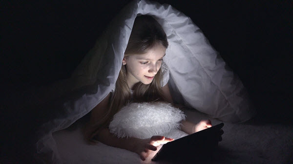Child viewing tablet in dark