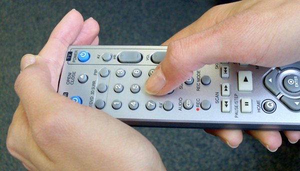 Covering the IR sensor of a remote with your hand. Illustration.