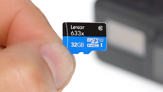 A microSD card held by fingertips.