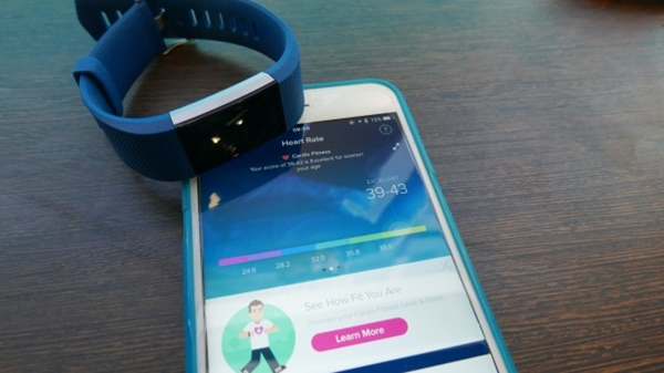 Fitbit Charge 2 laying next to a mobile device.