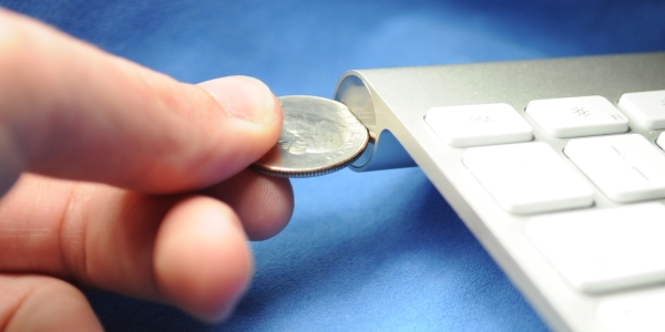 Using a coin to open the battery compartment cover of an Apple Wireless Keyboard.