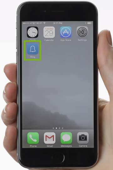 person holding phone with Ring app icon highlighted on phone