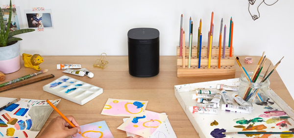 A sonos one on a desk surrounded by art supplies