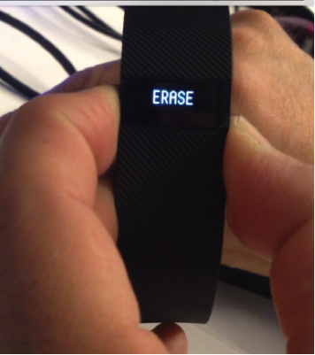 Fitbit Charge with ERASE on screen.