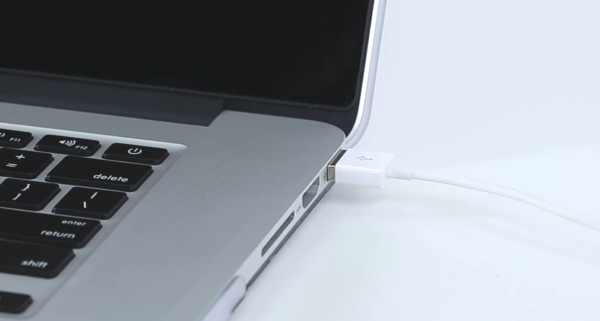 USB cable being plugged into computer.