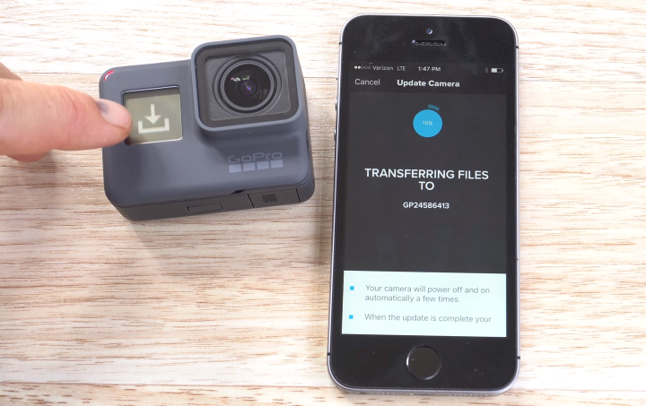 GoPro HERO6 displaying its update process, and a smartphone displaying it processing update files wirelessly to the GoPro.