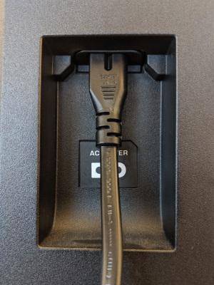 Power cord plugged into rear of VIZIO TV.