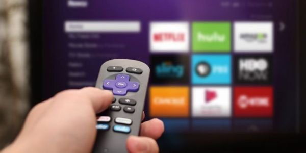 Roku remote pointed at TV screen.