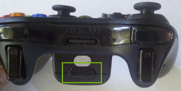 Xbox 360 wireless controller highlighting the battery compartment release button