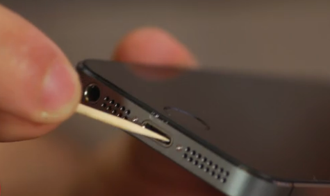 iPhone with a toothpick being used to clean out the charging port