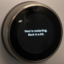 Nest thermostat performing a restart operation.