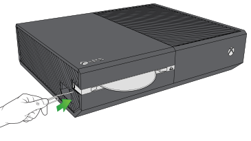 Paperclip being inserted in the left wall of the console.