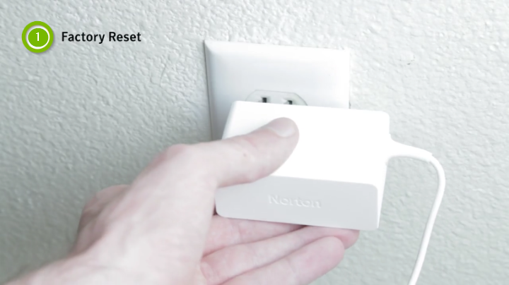 person holding plug in wall outlet