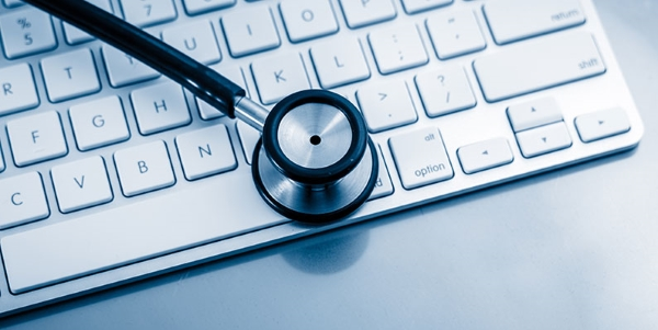 Mac keyboard with stethoscope on top.