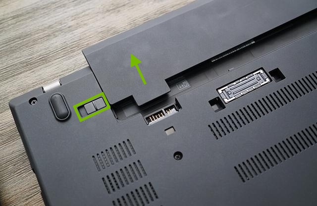 Battery being removed from laptop.