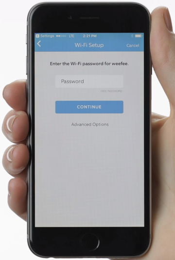 person holding a phone with wi-fi setup page and picture of password box