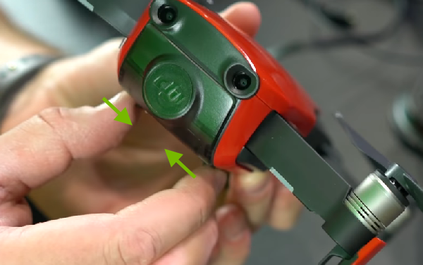 Arrows showing how to unlock gimbal cover.