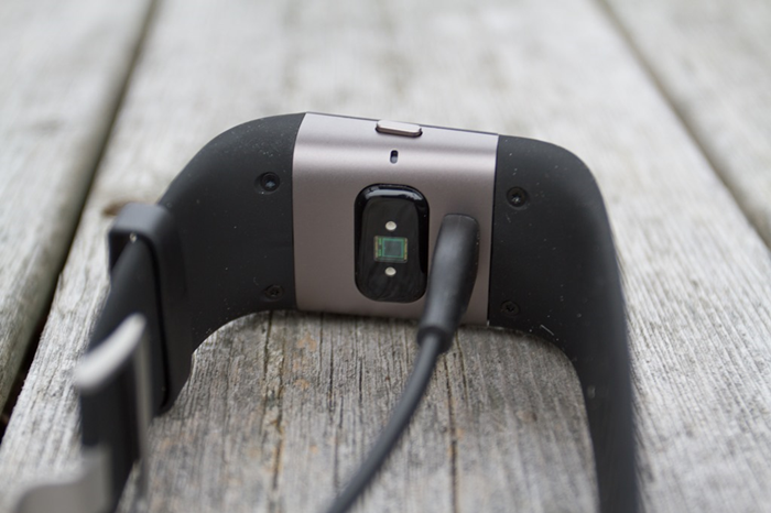 Fitbit Surge plugged in to charge with the supplied USB cable.