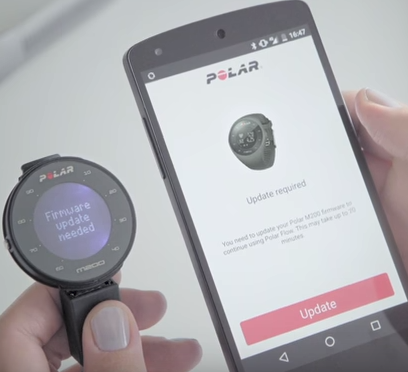 A polar m200 fitness tracker next to an android phone showing that an update is required